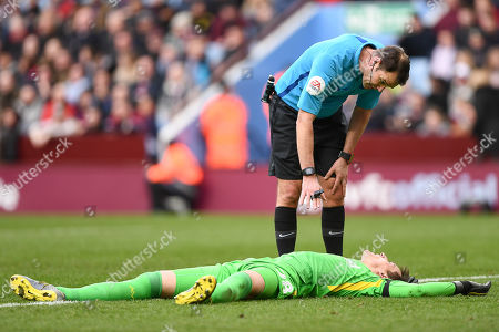 Referee James Linington looks over Lovre Kalinic (28) of Aston Villa after getting a knock to the head