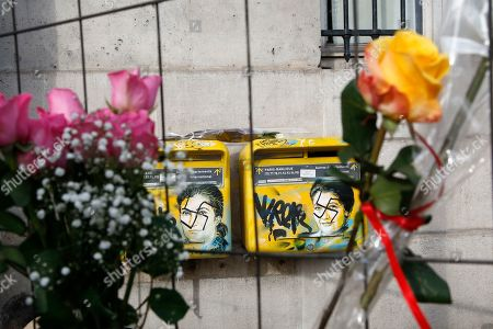 Roses are placed next to vandalized mailboxes with swastikas covering the face of the late Holocaust survivor and renowned French politician, Simone Veil, before their renovation in Paris, Tuesday Feb.12, 2019. According to French authorities, the total of registered anti-Semitic acts rose to 541 in 2018 from 311 in 2017, a rise of 74 percent