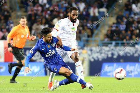 Al-Hilal player Hattan Bahebri (L) in action for the ball with Al-Qadisiyah player Nayef Hazazi  (R) during the Saudi Professional League soccer match between Al-Hilal and Al-Qadisiyah at King Saud University Stadium in Riyadh, Saudi Arabia, 12 February 2019.