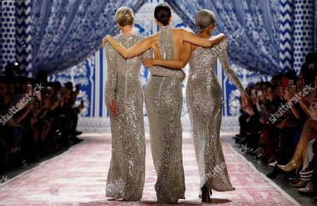 Models Karen Bjornson, left, Pat Cleveland, center, and Alva Chinn walk arm-in-arm after appearing on the runway at the conclusion of Naeem Khan's fashion show during New York Fashion Week, in New York