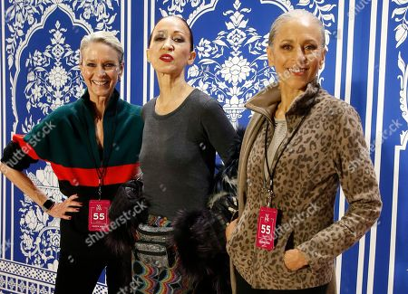 Models Karen Bjornson, left, Pat Cleveland, center, and Alva Chinn pose for a photo on the runway before modeling gowns for designer Naeem Khan during New York Fashion Week, in New York