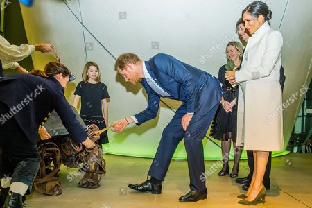 Getting their tickets from the mouth of a giant tortoise puppet - Prince Harry and Meghan Duchess of Sussex attend the gala performance of The Wider Earth in support of the Queen's Commonwealth Trust (QCT) and the production's official charitable partner, The Queen's Commonwealth Canopy (QCC).