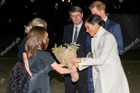 Sage Saunders, 12, gives flowers to Meghan with producer Trish Wadley - Prince Harry and Meghan Duchess of Sussex attend the gala performance of The Wider Earth in support of the Queen's Commonwealth Trust (QCT) and the production's official charitable partner, The Queen's Commonwealth Canopy (QCC).