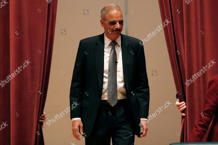 Former Attorney General Eric Holder walks onstage before speaking at Drake University, in Des Moines, Iowa