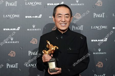 """Chinese director Zhang Yimou holds his award for Best Director at the 55th Golden Horse Awards in Taipei, Taiwan. The latest film from Zhang has been dropped from the Berlin International Film Festival for """"technical reasons."""" A notice on the official account of the movie """"One Second"""" on China's Weibo microblogging service apologized, but gave no details other than to say it was not possible to show the film at Berlin"""