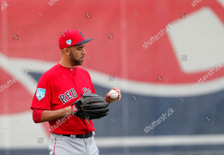 Boston Red Sox starting pitcher David Price looks at a ball as he warms up at the team's spring training baseball facility in Ft. Myers, Fla