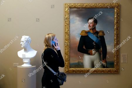 Stock Image of A visitor looks at Bust of Nicholas I (L) by German sculptor Christian Daniel Rauch and Portrait of Emperor Nicholas I (R) by Russian artist Wilhelm August Golicke during the exhibition 'Nicholas I' at the State Russian museum in St. Petersburg, Russia, 13 February 2019. The exhibition from the cycle 'The Romanovs Family Saga' covers the personality and state affairs of Emperor Nicholas I, as reflected in the works of painting, graphics, numismatics and decorative and applied arts from state museums and private collections. The exhibition will be open for visitors from 13 February to 20 May 2019.