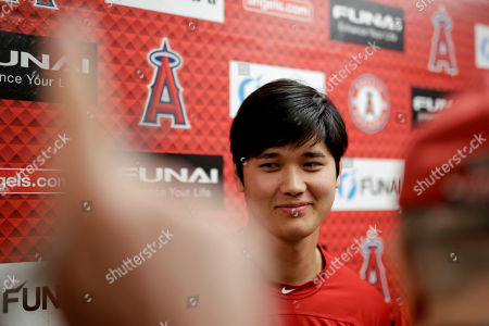 Los Angels Angels' Shohei Ohtani talks to the media at their spring baseball training facility in Tempe, Ariz., . The AL Rookie of the Year is recovering from Tommy John surgery