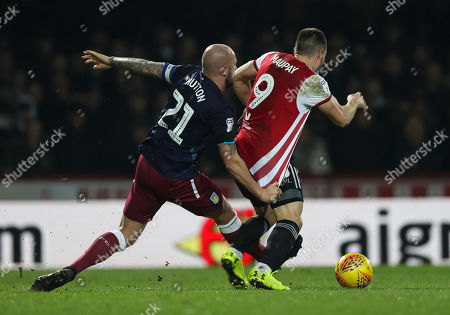 Alan Hutton of Aston Villa tugs the shirt of Neal Maupay of Brentford