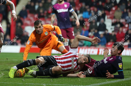 Neal Maupay of Brentford stretches for the ball whilst lying on the ground surrounded by Tyrone Mings, goalkeeper Lovre Kalinic and Tommy Elphick