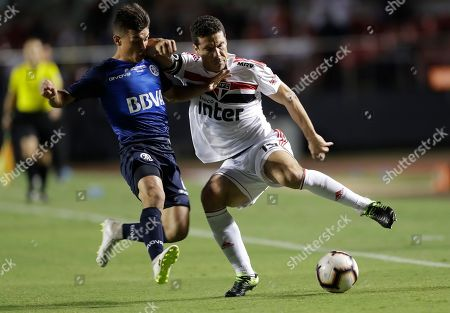 Hernanes of Brazil's Sao Paulo, right, fights for the ball with Andres Cubas of Argentina's Talleres, during a Copa Libertadores soccer match in Sao Paulo, Brazil