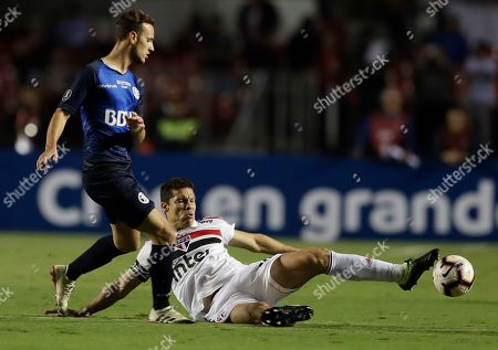 Hernanes of Brazil's Sao Paulo, right, fights for the ball with Tomas Pochettino of Argentina's Talleres, during a Copa Libertadores soccer match in Sao Paulo, Brazil