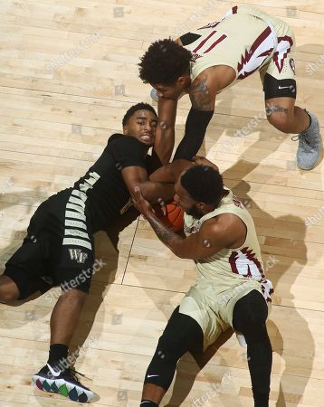 Wake Forest guard Brandon Childress, left, tries to stop Florida State guards David Nichols (11) and PJ Savoy, bottom right, from stealing the ball during the first half of an NCAA college basketball game in Tallahassee, Fla., . Florida State won 88-66