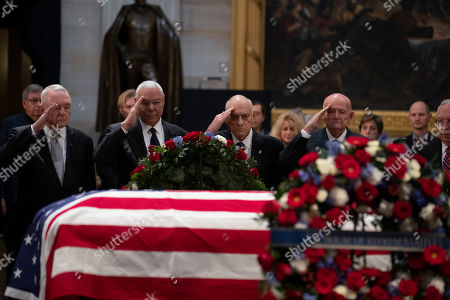 General Colin Powell, second from the left, pays his respects as he views the casket of President George H.W. Bush in the United States Capitol Rotunda on Capitol Hill in Washington, DC
