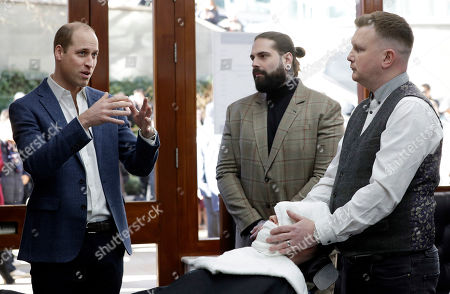 Britain's Prince William, left, speaks to Tom Chapman founder of the charity, centre, and barber Daniel Davies, right, during a visit to Pall Mall Barbers in London,. Prince William visited Pall Mall Barbers, Paddington Central, who are members of the Lions Barber Collective. The collective is an international group of top barbers who have come together to raise awareness for the prevention of suicide and provide training for barbers, called BarbersTalk