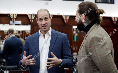 Stock Image of Prince William, left, speaks to Tom Chapman founder of the charity, during a visit to Pall Mall Barbers