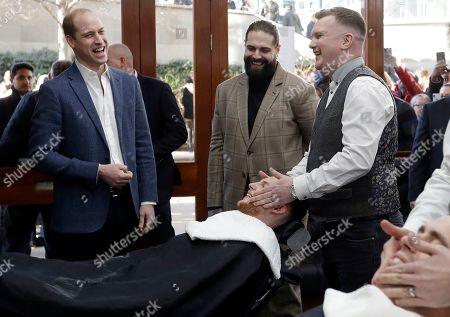 Prince William, left, speaks to Tom Chapman founder of the charity, centre, and barber Daniel Davies, right, during a visit to Pall Mall Barbers