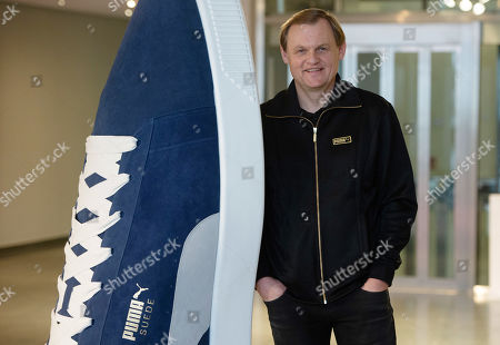 Bjorn Gulden, CEO of Puma, poses for a photo next oversized shoes after the annual earnings press conference in Herzogenaurach, Germany, 14 February 2019. The sporting goods manufacturer increased its sales in 2018 by 20.1 per cent to 1.226 million euros. The operating result (EBIT) is up to 38 million euros according to the management.