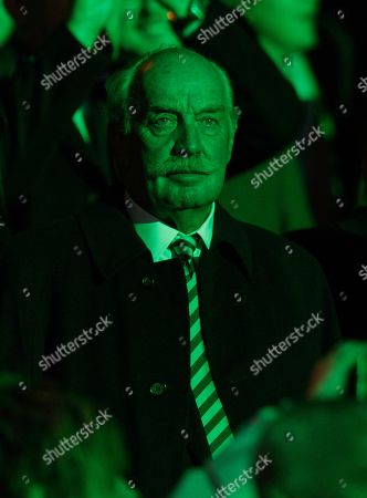 Dermot Desmond, Celtic's major shareholder, is bathed in green light as he watches the pre-match light show at Celtic Park.