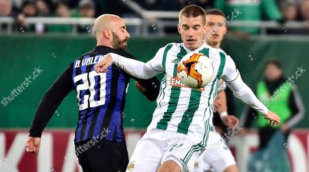 Inter midfielder Borja Valero, left, and Rapid's Srdjan Grahovac, right, challenge for the ball during the Europa League Round of 32 first leg soccer match between SK Rapid Vienna and Inter Milan in Vienna, Austria