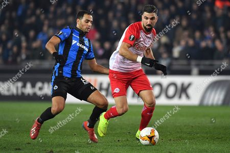 Salzburg's Munas Dabbur, right, runs with the ball past Brugge's Sofyan Amrabat during the Europa League round of 32 first leg soccer match between Club Brugge and Salzburg at the Jan Breydel stadium in Bruges, Belgium