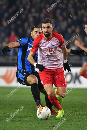 Stock Image of Salzburg's Munas Dabbur, right, vies for the ball with Brugge's Sofyan Amrabat during the Europa League round of 32 first leg soccer match between Club Brugge and Salzburg at the Jan Breydel stadium in Bruges, Belgium