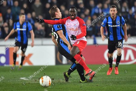 Salzburg's Diadie Samassekou, right, vies for the ball with Brugge's Ruud Vormer during the Europa League round of 32 first leg soccer match between Club Brugge and Salzburg at the Jan Breydel stadium in Bruges, Belgium