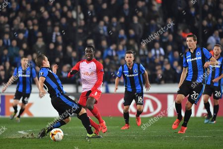 Salzburg's Diadie Samassekou, second left, vies for the ball with Brugge's Ruud Vormer, left, during the Europa League round of 32 first leg soccer match between Club Brugge and Salzburg at the Jan Breydel stadium in Bruges, Belgium