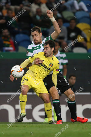 Villarreal's Manu Trigueros, front, and Sporting's Sebastian Coates both use their arms as they view for the ball during the Europa League round of 32, first leg, soccer match between Sporting CP and Villarreal at the Alvalade stadium in Lisbon