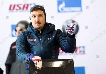 Stock Photo of Greg West, of the United States, gestures to a fan before taking a training run for the men's skeleton World Cup race, in Lake Placid, N.Y. Competition starts on Friday