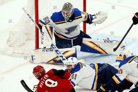 St. Louis Blues goaltender Jordan Binnington (50) makes a save on a shot by Arizona Coyotes center Clayton Keller (9) as Blues defenseman Robert Bortuzzo (41) and center Ryan O'Reilly (90) try to block the shot during the second period of an NHL hockey game, in Glendale, Ariz