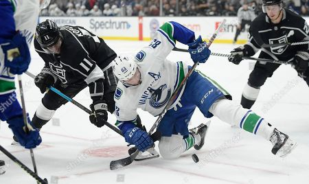 Los Angeles Kings center Anze Kopitar, left, and Vancouver Canucks center Jay Beagle, center, battle for a face-off as right wing Tyler Toffoli watches during the second period of an NHL hockey game, in Los Angeles