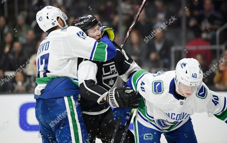 Los Angeles Kings right wing Tyler Toffoli, center, scuffles with Vancouver Canucks left wing Josh Leivo, left, and center Elias Pettersson during the overtime period of an NHL hockey game, in Los Angeles. The Canucks won in a shootout