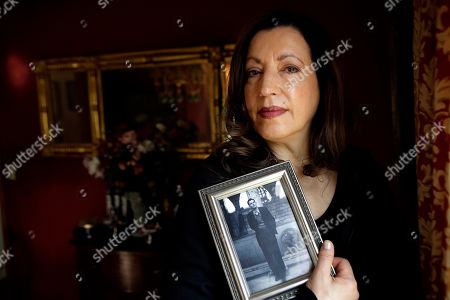 Christina Lamb, daughter of California wildfire victim Julian Binstock, holds a 1950s photo of her father at her home in Southborough, Mass. Initially, Binstock's children were told he was safely evacuated with over 100 other retirees on Nov. 8, which made the subsequent news of his death even more devastating, said Christina
