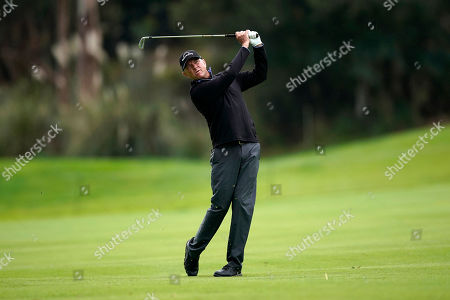Stock Picture of Davis Love III hits his second shot on the 18th hole as first round play continues during the Genesis Open golf tournament at Riviera Country Club, in the Pacific Palisades area of Los Angeles