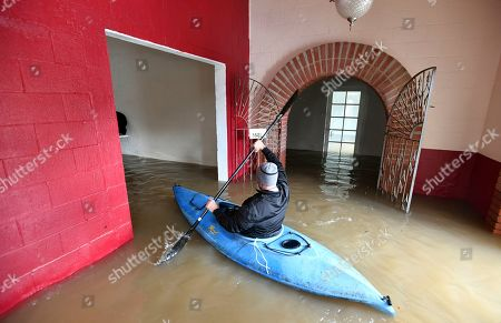 Jay Michael Tucker kayaks through the flooded Surrey Resort as the Russian River flows through it in Guerneville, Calif., on . Streets and low-lying areas flooded as the Russian River swelled above its banks today