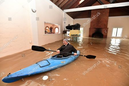 Stock Photo of Jay Michael Tucker kayaks through the flooded Surrey Resort as the Russian River flows through it in Guerneville, Calif., . Streets and low-lying areas flooded as the Russian River swelled above its banks today