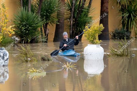 Stock Image of Jay Michael Tucker kayaks through the flooded Surrey Resort as the Russian River flows through it in Guerneville, Calif., . Streets and low-lying areas flooded as the Russian River swelled above its banks today