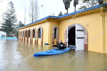 Jay Michael Tucker kayaks through the flooded Surrey Resort as the Russian River flows through it in Guerneville, Calif., . Streets and low-lying areas flooded as the Russian River swelled above its banks Friday