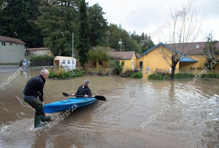 Owner Alex Yarosheno, left, pulls Jay Michael Tucker, right, shore as the Russian River flows through his resort in Guerneville, Calif., . Streets and low-lying areas flooded as the Russian River swelled above its banks Friday