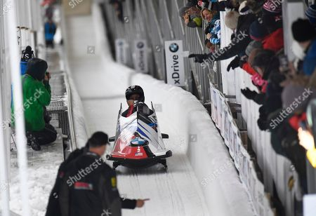 Driver Elana Meyers Taylor, front, and brakeman Lake Kwaza, of The United States, arrive in the finish area after their second run in the women's bobsled World Cup, in Lake Placid, N.Y. Meyers and Kwaza won the event