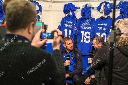 AFC Wimbledon striker James Hanson (18) talking to Martin Keown during the The FA Cup 5th round match between AFC Wimbledon and Millwall at the Cherry Red Records Stadium, Kingston
