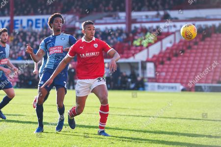 Jacob Brown of Barnsley (33) and Sido Jombati of Wycombe Wanderers (2) watch the loose ball in the area during the EFL Sky Bet League 1 match between Barnsley and Wycombe Wanderers at Oakwell, Barnsley