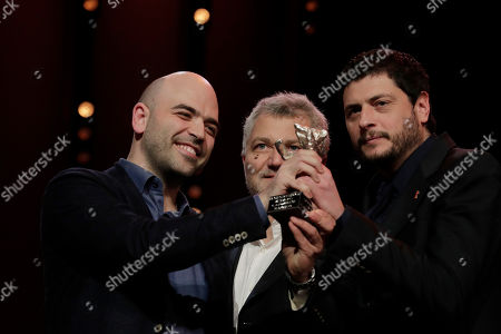 Roberto Saviano, Claudio Giovannesi, Maurizio Braucci. Writers Roberto Saviano, from left, Maurizio Braucci and Claudio Giovannesi hold the silver bear best screenplay award for the film 'Piranhas' onstage at the award ceremony of the 2019 Berlinale Film Festival in Berlin, Germany