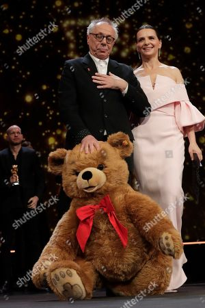 Dieter Kosslick, Juliette Binoche. Festival director Dieter Kosslick, left, receives a parting gift of a teddy bear from jury president Juliette Binoche on the occasion of his eighteenth and final Berlinale, at the award ceremony of the 2019 Berlinale Film Festival in Berlin, Germany