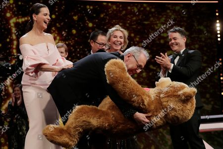 Dieter Kosslick, Juliette Binoche. Festival director Dieter Kosslick, centre, embraces a teddy bear given by jury members on the occasion of his eighteenth and final Berlinale, at the award ceremony of the 2019 Berlinale Film Festival in Berlin, Germany
