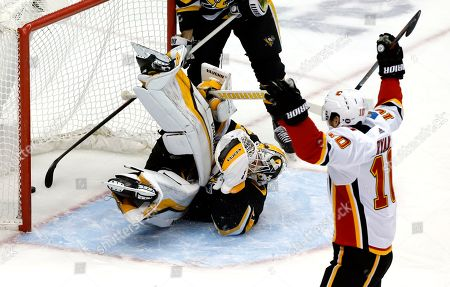 Calgary Flames' Derek Ryan (10) celebrates after teammate Andrew Mangiapane put a shot behind Pittsburgh Penguins goaltender Matt Murray (30) for a goal in the first period of an NHL hockey game in Pittsburgh