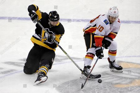 Pittsburgh Penguins' Brian Dumoulin (8) pokes the puck off the stick of Calgary Flames' Derek Ryan (10) in the third period of an NHL hockey game in Pittsburgh, . The Flames won 5-4