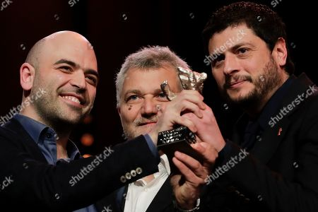 From left, writers Roberto Saviano, Maurizio Braucci and Claudio Giovannesi hold the silver bear best screenplay award for the film 'Piranhas' onstage at the award ceremony of the 2019 Berlinale Film Festival in Berlin, Germany