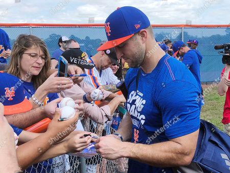 New York Mets' Tim Tebow signs autographs at spring training baseball practice, in Port St. Lucie, Fla